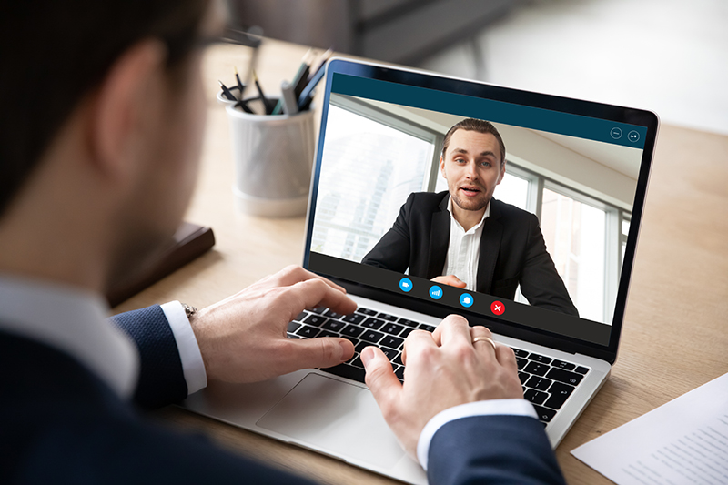 Two businessmen speaking through video chat